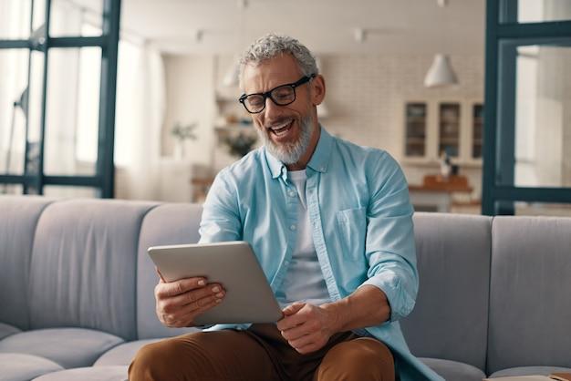 디지털 태블릿을 사용하고 집에서 소파에 앉아있는 동안 웃고 편안한 수석 남자