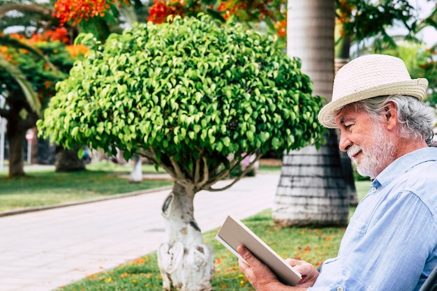 Relaxed senior man with white beard smiles sitting in the park reading a book
