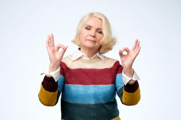 Расслабленная старшая женщина наслаждается мирной атмосферой, держит руки в знаке мудры