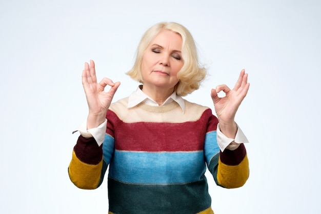 Relaxed senior woman enjoys peaceful atmosphere, keeps hands in mudra sign