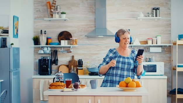 Relaxed senior woman listening music on headphones during breakfast in kitchen. elderly dancing, fun lifestyle with modern technology
