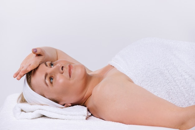 Relaxed senior woman in salon after spa body and facial treatments. white background with space. high quality photo
