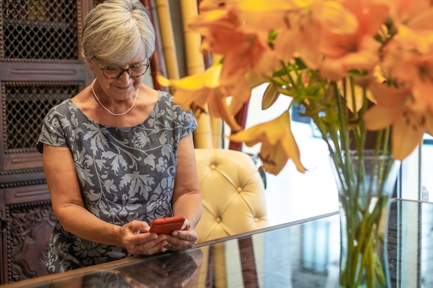 Relaxed senior woman using mobile phone for messages. retiree white haired sitting inside smiling