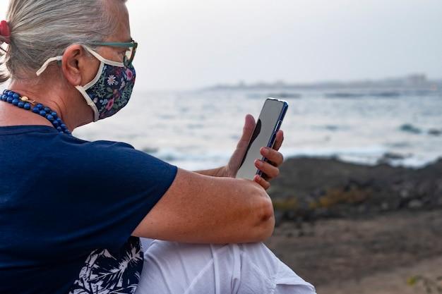 Расслабленная пожилая женщина с цветочной маской из-за коронавируса сидит на открытом воздухе на закате с помощью смартфона, горизонт над водой - концепция активных пожилых людей во время выхода на пенсию