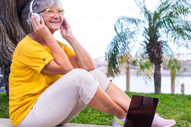 Relaxed senior woman with headphones sitting outdoors  smiling. laptop computer on bench