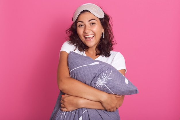 Relaxed sensual happy young woman hugging gray pillow, looking at camera with charming smile