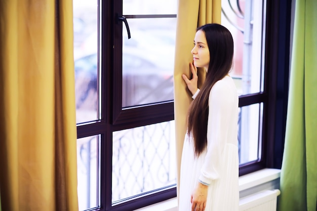 Расслабленная безмятежная симпатичная молодая женщина дома, счастливая спокойная мечта леди наслаждается благополучием, дыша свежим воздухом в уютном доме