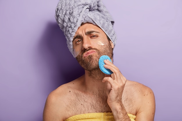 Relaxed serious man with stubble wipes skin on face after shower, holds cosmetic sponge, wrapped in soft towel