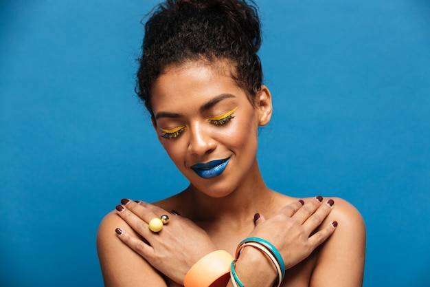 Relaxed smiling afro woman with fancy makeup and accessories posing with closed eyes and crossed hands on chest, over blue wall