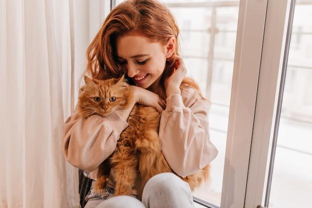 그녀의 솜 털 고양이와 놀고 편안 하 게 웃는 소녀. 애완 동물을 들고 놀라운 아가씨의 실내 샷.