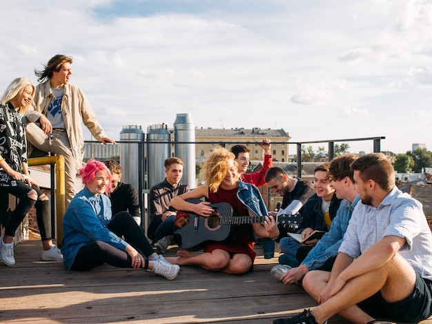 Relaxed smiling young people travel europe. sitting on a rooftop singing and enjoying their trip. youth lifestyle