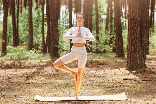 Relaxed sporty woman standing in open air with closed eyes keeping palms together, standing on one leg, wearing sportswear, enjoying training in beautiful forest. Free Photo