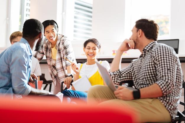 편안한 학생들. 수업에 앉아 웃고있는 동안 웃고 기뻐하는 긍정적 인 감정적 인 학생들