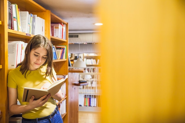 Relaxed teenager reading book in library