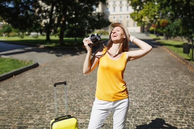 모자에 눈을 감고 머리에 손을 얹고 있는 편안한 여행자 관광 여성은 야외에서 복고풍 빈티지 사진 카메라를 들고 있습니다. 주말 휴가에 해외 여행을 하는 소녀. 관광 여행 라이프 스타일.