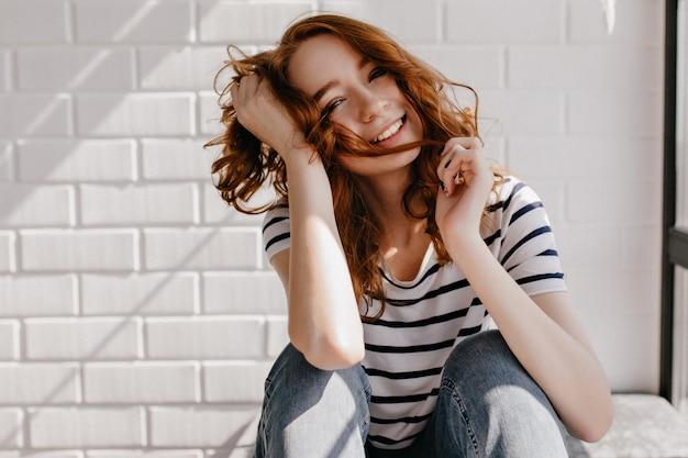 座ってリラックスした身なりのよい女の子。彼女の生姜髪で遊んでいる見事な白人女性。