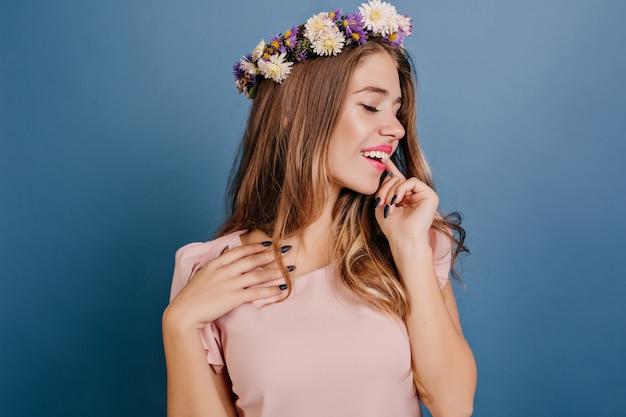 Donna bianca rilassata in cerchietto di fiori in posa con gli occhi chiusi