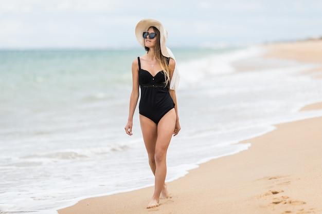 Donna rilassata in bikini che gode delle vacanze estive della spiaggia tropicale.