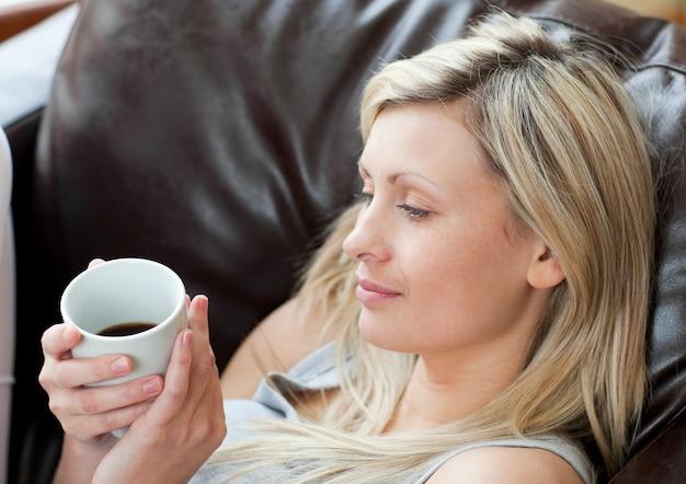 ソファに座っているリラックスした女性のコーヒーを飲む