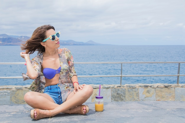 Relaxed woman during summer vacations, sitting on the seafront, in a bikini and with a fresh juice in the glass. copyspace on right side.