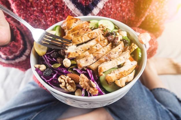 家で鶏の胸肉サラダを楽しむリラックスした女性