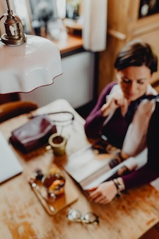 Donna rilassata che si gode una rivista in un bar