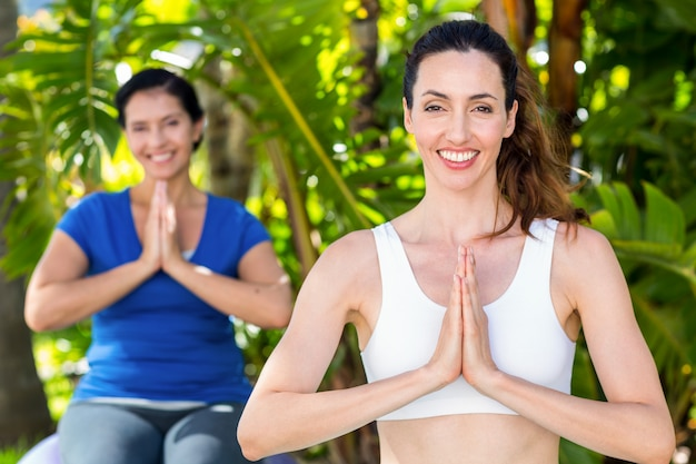 Relaxed woman and her trainer doing yoga