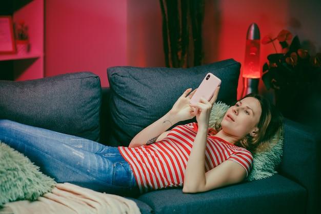 Расслабленная женщина, держащая смартфон с помощью мобильных приложений, смотрит смешное видео, смеясь, лежа на диване