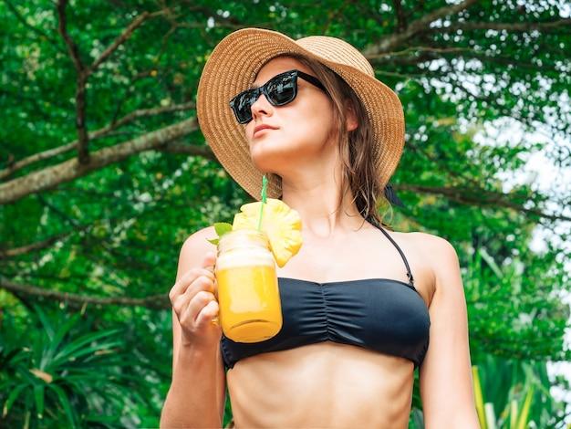 Расслабленная женщина в бикини наслаждается тропическим курортом, пьет ананасовый коктейль