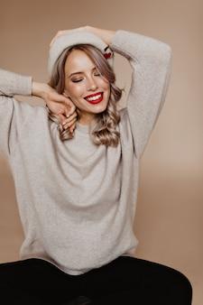 Расслабленная женщина в мягком коричневом свитере смеется в студии