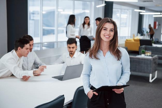 室内でリラックスした女性。バックグラウンドで従業員とオフィスに立っている若い女の子の肖像画