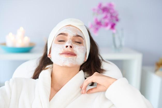 La donna rilassata sta ottenendo una maschera facciale nella spa