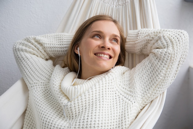 Relaxed woman listening to music in earphones