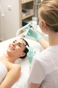 그녀의 얼굴에 미세 전류 치료 절차를 갖는 동안 기뻐하고 웃는 편안한 여자