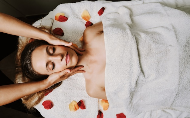 Relaxed woman lying on spa bed for facial and head massage