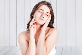 Relaxed woman pressing hands to face