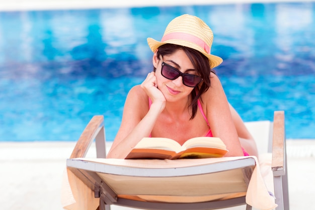 Relaxed woman reading a book with swimming pool background