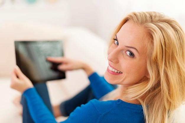 Donna rilassata che si siede sul divano con tavoletta digitale