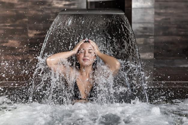 Расслабленная женщина брызгает водой под струей водопада
