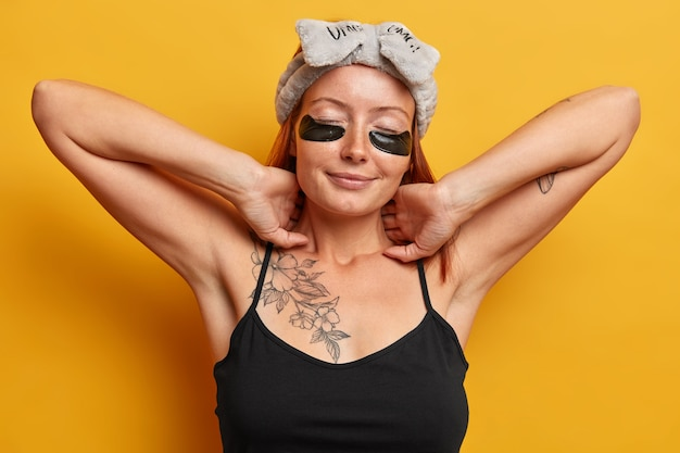 リラックスした女性は伸び、目の下にコラーゲン保湿パッチをつけ、首に優しく触れ、黄色い壁に隔離されたヘアバンドと黒いtシャツを着ています。フェイシャルスキンケアと美容トリートメント