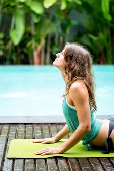 Relaxed woman stretching back near swimming pool