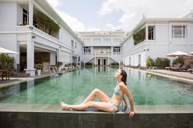 호텔에서 수영장 가장자리에 일광욕 편안한 여자
