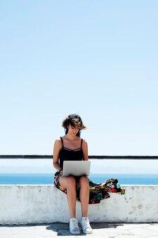 夏にノートパソコンでタイピングリラックスした女性