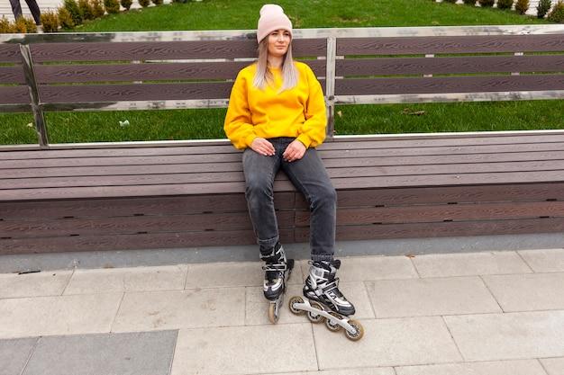 Лезвия ролика расслабленной женщины нося сидя на стенде