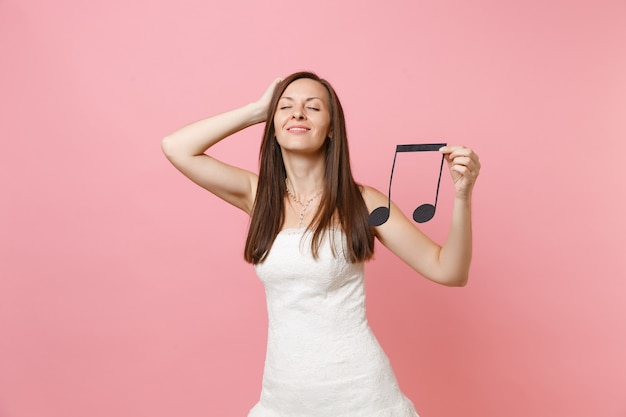 Relaxed woman in white dress keeping hand on head holding musical note, choosing staff musicians or dj