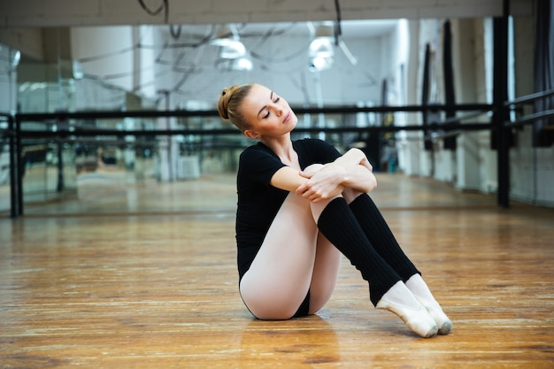 Relaxed woman with closed eyes resting in ballet class