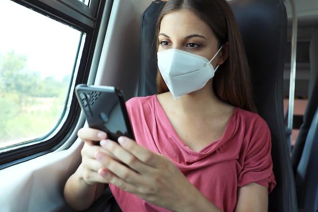 スマートフォンアプリを使用してフェイスマスクでリラックスした女性