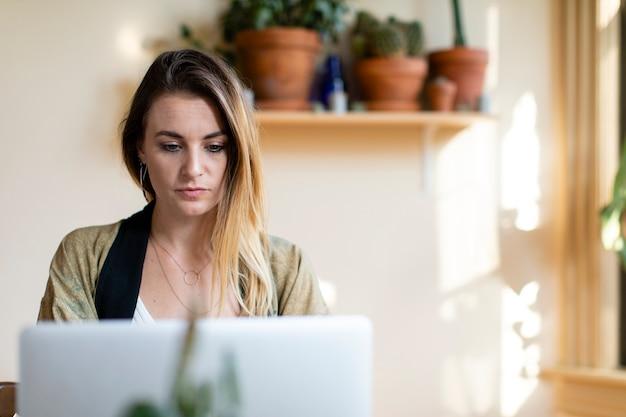 Donna rilassata che lavora da casa sul suo laptop