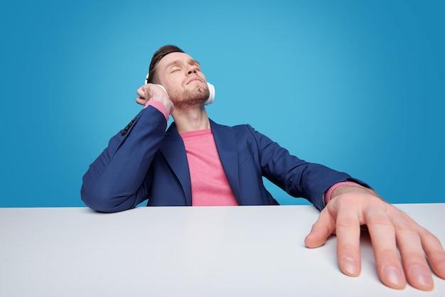Расслабленный молодой бородатый мужчина сидит с закрытыми глазами за столом и слушает вдохновляющую музыку в наушниках