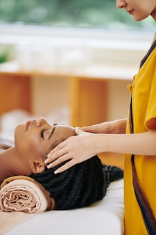 Relaxed young black woman enjoying head massage in spa salon
